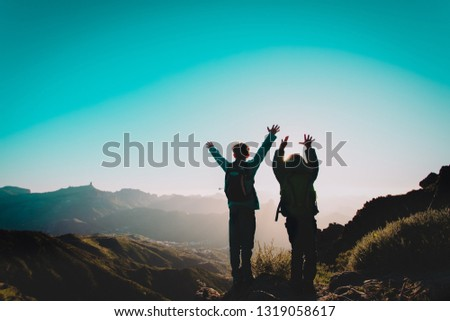 happy boy and girl travel in mountains at sunset, kids enjoy hiking #1319058617