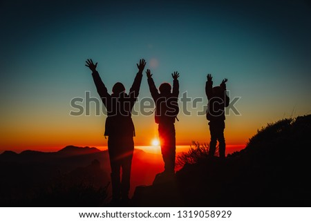 Silhouettes of father and kids hiking at sunset, family travel in nature #1319058929