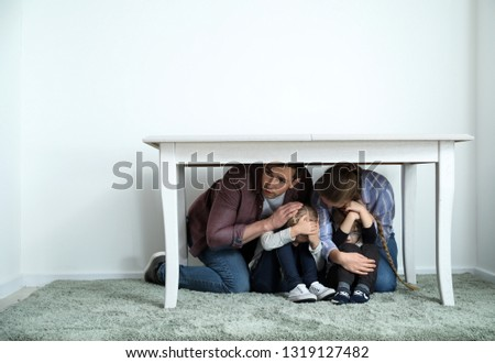 Family under table during earthquake indoors Royalty-Free Stock Photo #1319127482