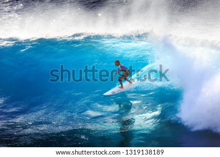 MADEIRA, PORTUGAL - OCTOBER 8, 2015: Surfer riding the big blue surf waves on the island Madeira, Portugal, a popular surfing tourist destination on October 8, 2015 #1319138189
