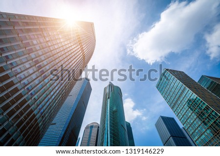 Bottom view of modern skyscrapers in business district against blue sky #1319146229
