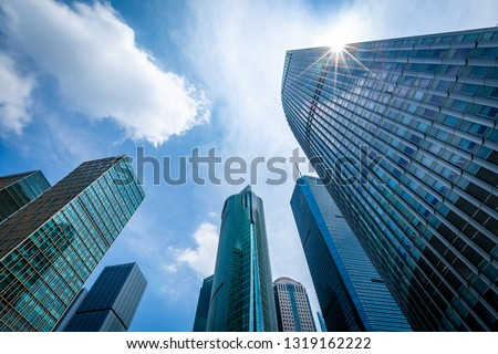 Bottom view of modern skyscrapers in business district against blue sky #1319162222