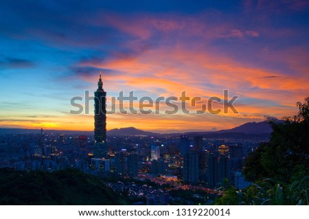 Taipei, Taiwan - August 6, 2008: Sunset moments, golden clouds and blue sky, Taipei city urban night scene, architectural brilliant lights. #1319220014