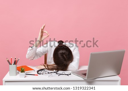 Female doctor laid her head down on desk, work on computer, medical document in hospital isolated on pastel pink background. Woman in medical gown stethoscope show ok. Healthcare medicine concept #1319322341