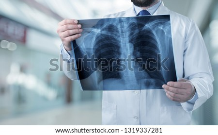 Young man doctor holding x-ray #1319337281