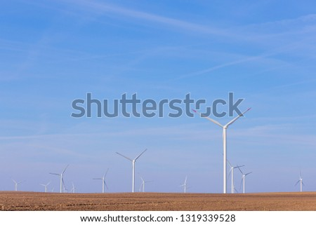 Windmill turbine farm with partly cloudy blue sky in background. Renewable energy wind turbines #1319339528
