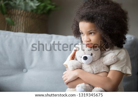 Upset lonely bullied little african american kid girl holding teddy bear looking away feels abandoned abused, sad alone preschool mixed race child orphan hugging stuffed toy, charity adoption concept #1319345675