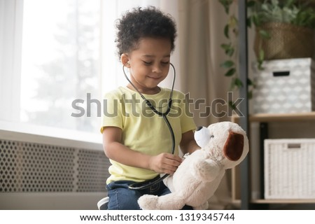 Cute little toddler african american boy playing funny game as doctor holding stethoscope listening to toy, mixed race black preschool child kid pretending nurse treating fluffy patient at home #1319345744
