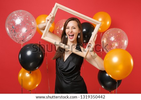 Cheerful young woman in little black dress celebrating and holding picture frame on bright red background air balloons. International Women's Day, Happy New Year birthday mockup holiday party concept
