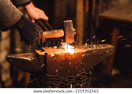 The blacksmith manually forging the red-hot metal on the anvil in smithy with spark fireworks #1319352563