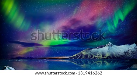 Gorgeous, unreal beautiful night view of the reflection of the northern lights in the water of the ocean and snow-capped mountains. Night Northern Lights is just an amazing sight. #1319416262