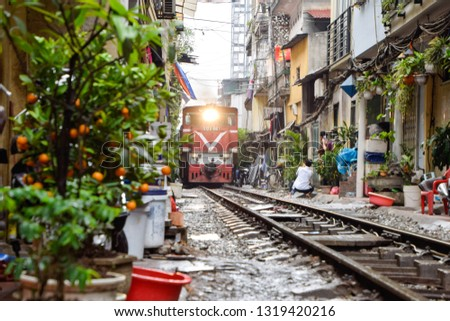 Popular place and one of the main attraction of Hanoi, Vietnam City. Train passing through the narrow street between old many houses in Hanoi. Way of life of people in Hanoi, Vietnam City, Blur Image. #1319420216