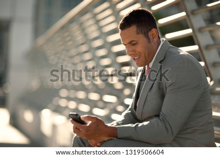 Smiling mid adult business man sending a text message on his phone. #1319506604