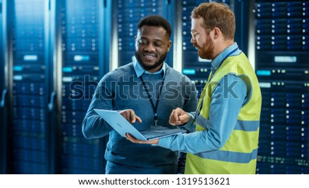 Bearded IT Specialist in Glasses and High Visibility Vest with a Laptop Computer and Black Technician Colleague Talking in Data Center while Standing Next to Server Racks. Running Diagnostics. #1319513621
