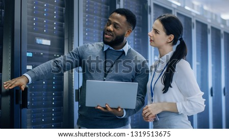 Black IT Technician with a Laptop Computer Gives a Tour to a Young Intern. They Talk in Data Center while Walking Next to Server Racks. Running Diagnostics or Doing Maintenance Work. #1319513675