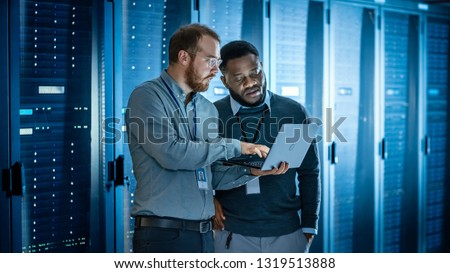 Bearded IT Technician in Glasses with Laptop Computer and Black Male Engineer Colleague are Using Laptop in Data Center while Working Next to Server Racks Running Diagnostics or Doing Maintenance Work Royalty-Free Stock Photo #1319513888