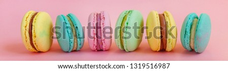 Sweet almond colorful unicorn pink blue yellow green macaron or macaroon dessert cake isolated on trendy pink pastel background. French sweet cookie. Minimal food bakery concept. Banner #1319516987