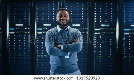 Bearded Black IT Engineer Standing and Posing with Crossed Arms in the Middle of a Working Data Center Server Room with Server Computers Working on a Rack. #1319520923