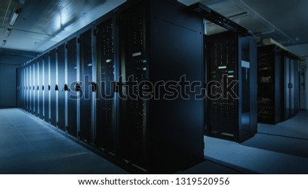 Shot of a Working Data Center With Rows of Rack Servers. Led Lights Blinking and Computers are Working. Dark Ambient Light. #1319520956