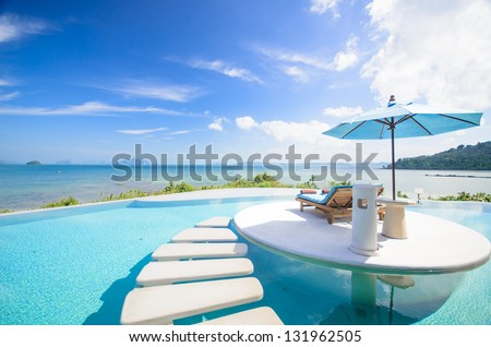beach chair with umbrella on private pool, ocean view #131962505