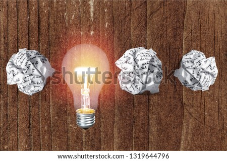 Glowing glass light bulb on wooden background #1319644796