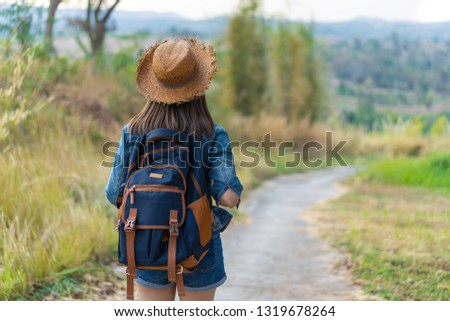 woman with backpack walking on footpath in the nature #1319678264