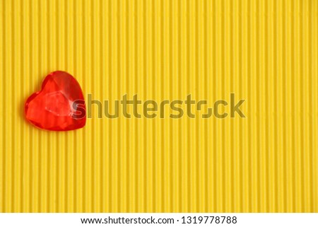 red plastic heart on yellow corrugated background with vertical pattern on left side, sign of love and romance, greeting card for womens day or valentine