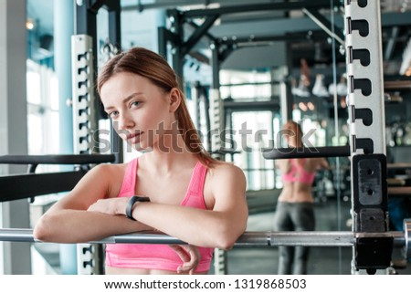Young woman in gym healthy lifestyle standing leaning on trainer looking camera playful relaxed #1319868503