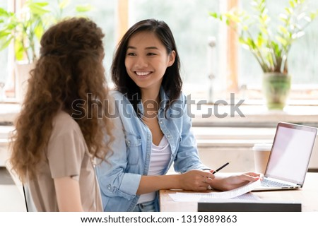 Smiling asian hr insurer advisor meeting applicant at job interview consulting client about contract offer giving advice, happy diverse girls colleagues interns students discussing paperwork together #1319889863