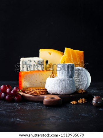 Cheese assortment: blue cheese, hard cheese, soft cheese on a cutting board. Slate black background. Copy space. #1319935079