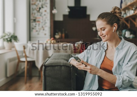 Technology in our life. Waist up portrait of young happy woman on sofa watching video on mobile phone with wireless earbuds #1319955092