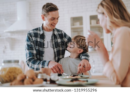 Cheerful boy turning his head and looking at his father while getting his help #1319955296