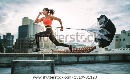 Female athlete training on terrace of a building with a parachute tied behind her. Fitness woman running hard with a drag parachute on rooftop with sun flare in the background. #1319981120
