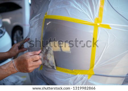 Repairing car body by puttying close up work after the accident by working sanding primer before painting. , The mechanic repair the car  , Using plastic putty ,Prepare surface for spray painting #1319982866