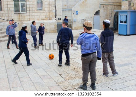 JERUSALEM, ISRAEL - February 14, 2019. Group of playful young Jewish boys with religious yarmulke are playing football match together in Jewish Quarter of the old city.  #1320102554