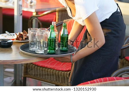 A waitress is holding a tray with dirty dishes and leftover food. Waitress cleaning the table in a restaurant. The concept of service. #1320152930