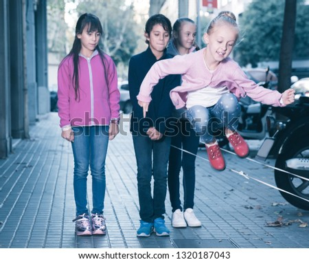 Positive children play on city sidewalk in autumn city #1320187043