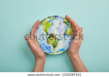 top view of woman holding planet picture on turquoise background, earth day concept