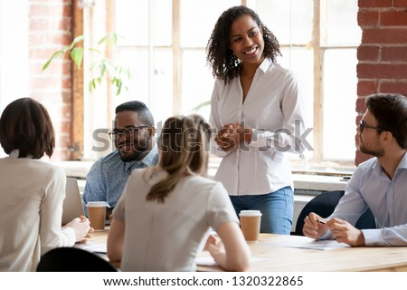 Multinational businesspeople gathered together at modern office conference boardroom partners during business meeting, black african female team leader ready to speak standing looking at colleagues #1320322865