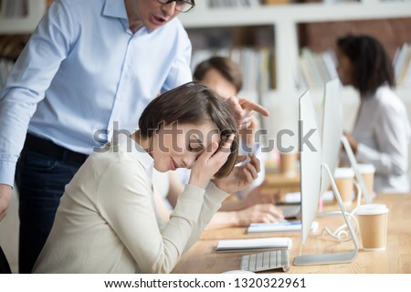 Angry irritated company boss reprimanding employee female, accusing of serious mistake and bad work. Young crying woman worker listening yelling from executive manager feels guilty frustrated unhappy #1320322961