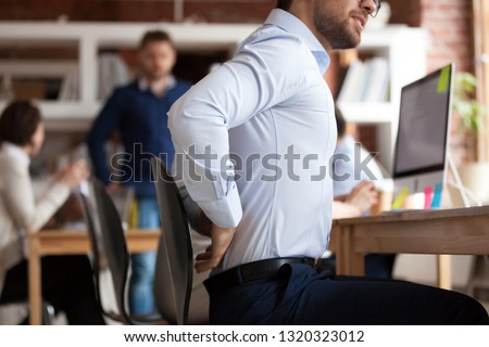 Businessman working sitting at desk feels unhealthy suffers from lower back pain. Damage of intervertebral discs, spinal joints, compression of nerve roots caused by wrong posture and sedentary work #1320323012