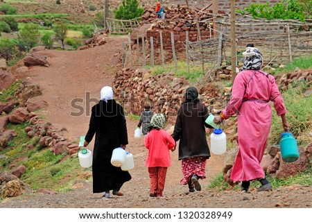 Africa - Moroccan Arab women with veils on their heads bring water into drinking plastic bottles in their homes - poverty and lack of water and basic necessities #1320328949