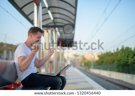 Young Happy Tourist Man Using Laptop With Fist Raised At The Train Station #1320456440