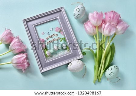 easter flat lay with bunch of pink tulips,painted eggs and  happy easter greeting card in a frame on mint background