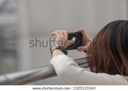 Young brunette girl taking picture with smartphone on city #1320533363