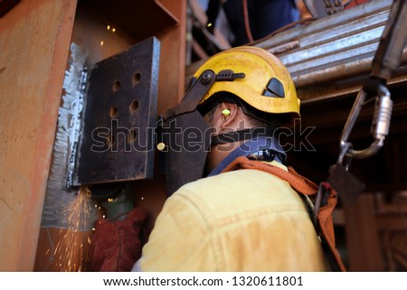 Side view of welder wearing safety helmet, fall arrest harness ear plug using locking Karabiner which attached with retraceable lanyard device back of his safety harness loop fall safety prevention    #1320611801