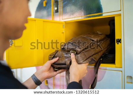 business man hand push bag using Electronic Locker on Yellow automated parcel terminal E locker on the street  home delivery.  #1320615512