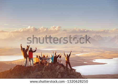 Large group of happy friends is having fun on mountain top and looks at mountain's valley. Adventure or travel concept #1320628250