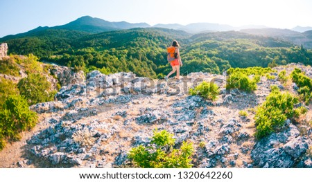 Girl at the top of the mountain. A woman with a backpack walks along a mountain path. Climb to the top. Travel to picturesque places. Tourist against the sky and the sea. #1320642260