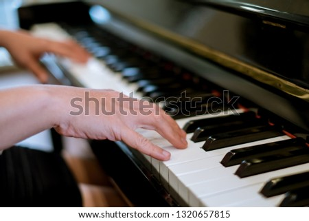 Close-up of a music performer's hand playing the piano  #1320657815